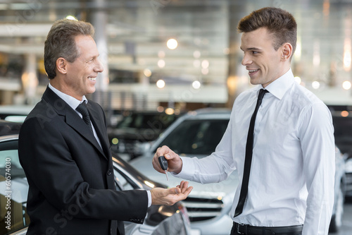 Giving a key of a brand new car.