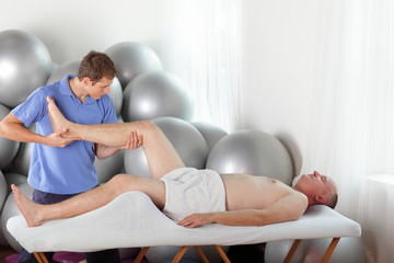 manual therapy - physiotherapist bending male patient knee