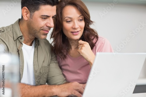 Couple using laptop in the kitchen