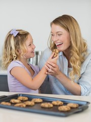 Girl feeding cookie to mother
