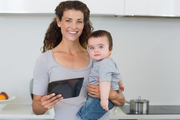 Mother carrying baby boy while holding digital tablet