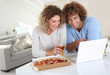 Couple eating pizza and websurfing on internet