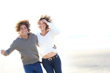 Cheerful couple running on the beach