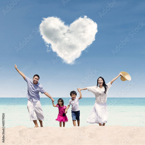 Happy family run at beach under love cloud