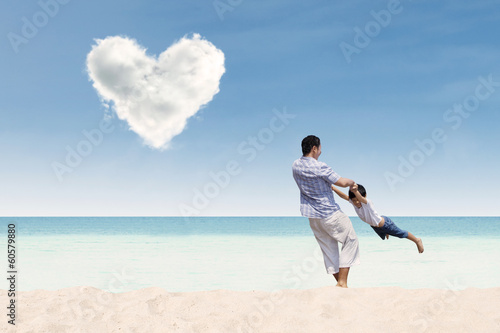 Happy father and son with love cloud at beach