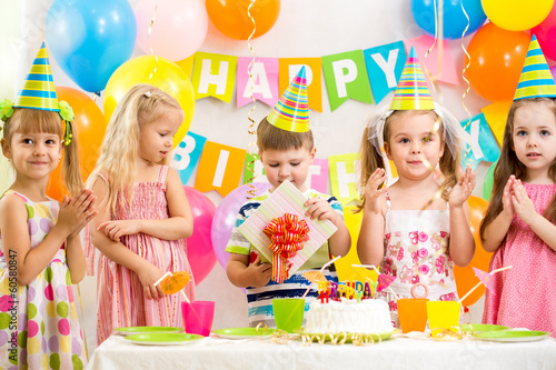 boy with gift and group of kids at birthday party