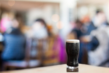 Pint of stout in busy restaurant