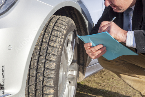 Man with paper block kneeling on car tires