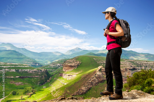 Female hiker on rocky cliff.