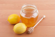 Fresh honey in a glass jar and lemons.