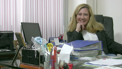 Busy businesswoman working and smilin to camera