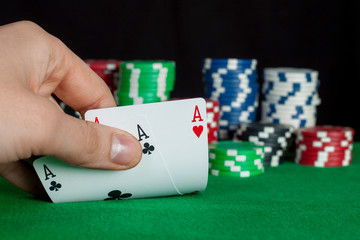 player checks his hand, two aces in, focus on card