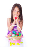 Little girl with basket full of colorful eggs