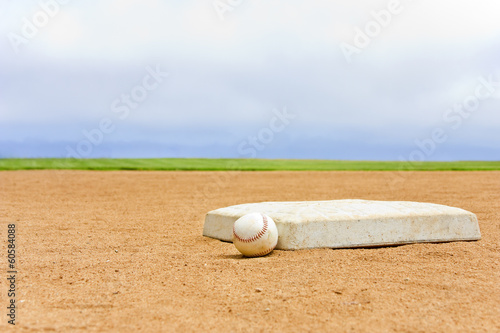 Baseball field base and ball, blue sky background