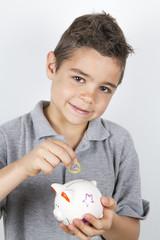 Bambino mette un euro nel salvadanaio