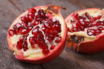 cut ripe pomegranate on an old wooden table. horizontally