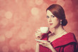 Beautyful redhead women with cup of tea.