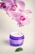 Face/hand cream jar and purple orchid flowers, vertical shot