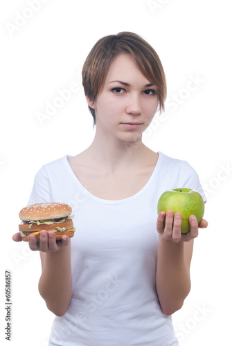 Girl makes choice between apple and hamburger