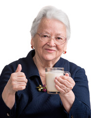 Healthy old woman holding a glass milk