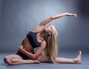 Image of smiling young woman doing stretching