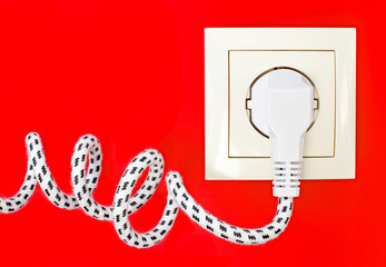 Power cord and power socket against a red background