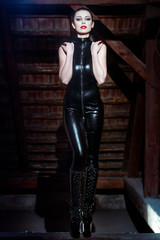 Sexy emotional dominatrix posing in catsuit