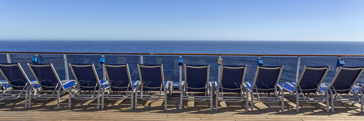 Lounge chairs on deck of luxury cruise ship