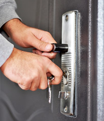 Hands inserting keys in door lock