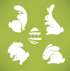 white Easter rabbits silhouettes on green background