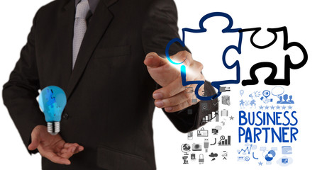 businessman hand drawing Partnership Puzzle Concept