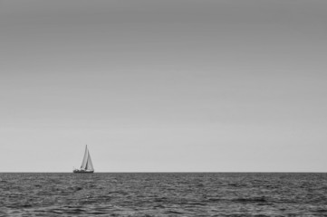 Sailboat alone at open sea black and white