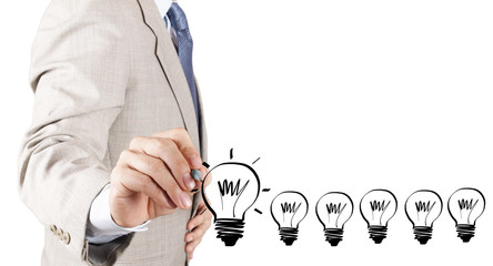 business man hand drawing idea light bulb as concept