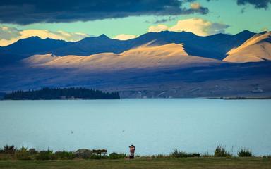 Woman taking photo at lake, New zealand