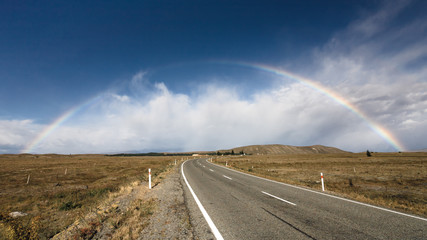 Beautiful full rainbow over road and mountain, New Zealand
