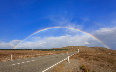 Beautiful full double rainbow over road and mountain