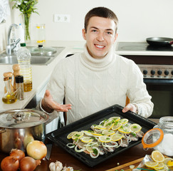 Handsome man with raw fish on roasting pan