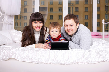 Happy family using the tablet lying on bed.
