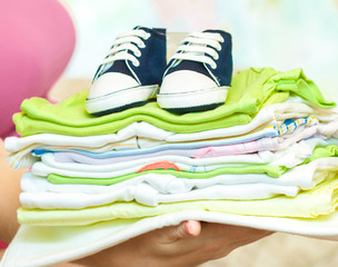 Woman holding stack of children's clothing