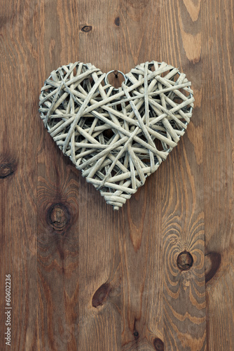 Reed heart hanging against a rustic wooden background.