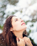 Young smiling woman on winter forest background  looking up
