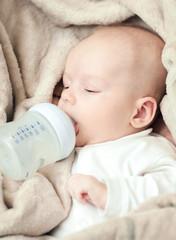 newborn baby sucking bottle