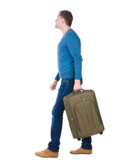 back view of walking  man in pullover with suitcase.