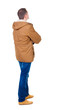 Back view of handsome man in winter parka looking