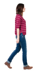 back view of walking  woman in striped sweater.