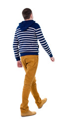 Back view of walking handsome man in jeans and striped sweater.