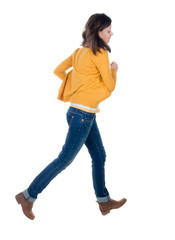 back view of running  woman in yellow cardigan