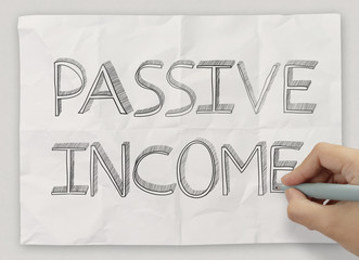 close up of hand drawing passive income on crumpled paper backgr