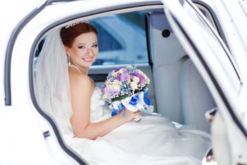 Smiling happy young bride sitting in white limo.