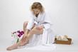 Wellness - Junge Frau trägt Körperöl auf ihr Bein auf